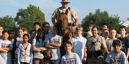 Mounted patrol officer with children.